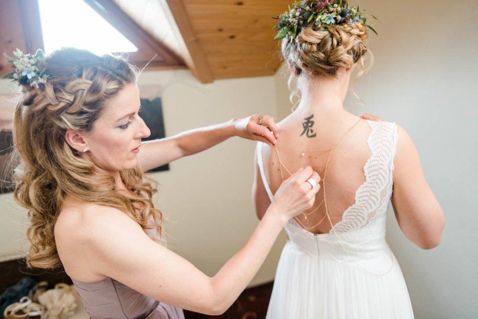 Getting ready - Braut mit rückenfreiem Boho Brautkleid kriegt Boho Rückenkette angelegt