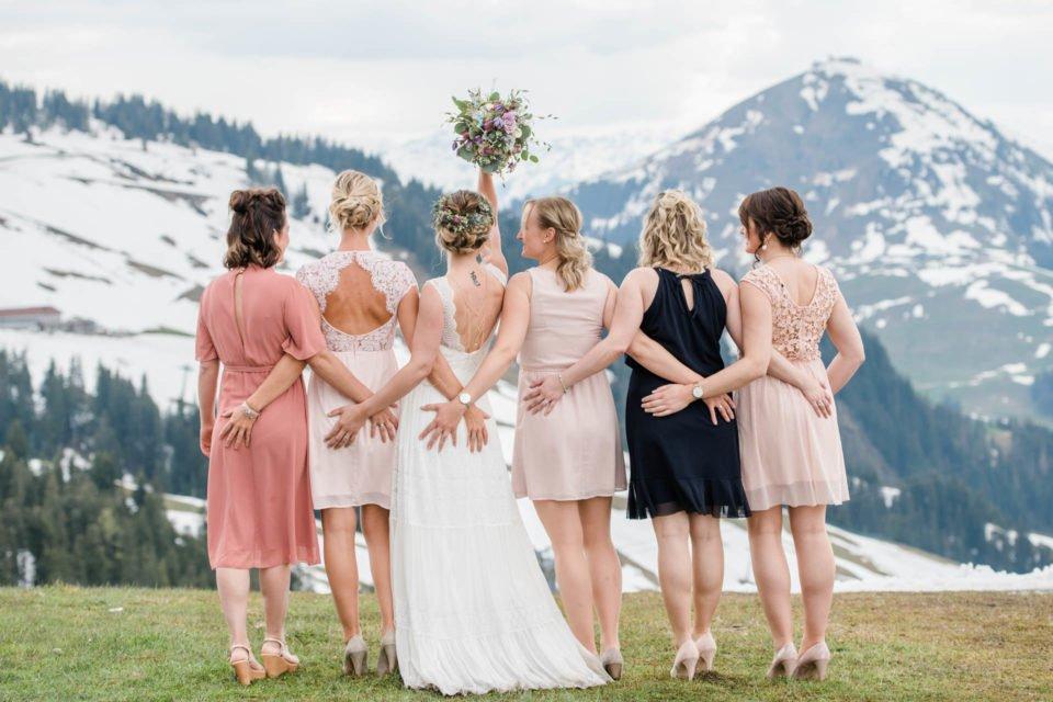 Braut mit Brautstrauß zwischen Brautjungerfen vor Bergpanorama