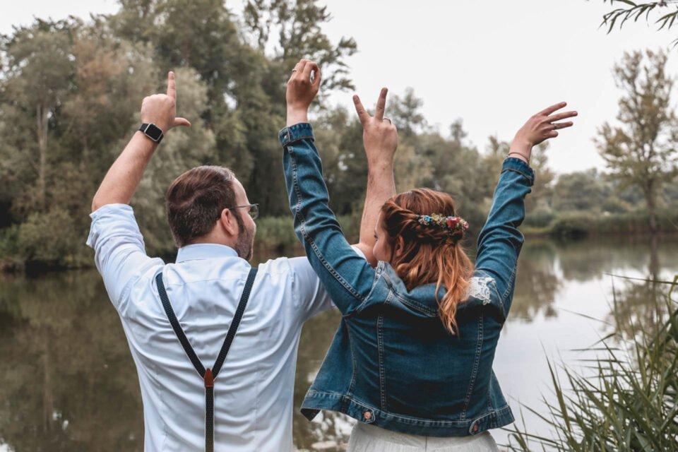 Brautpaar von hinten vor einem See fotografiert