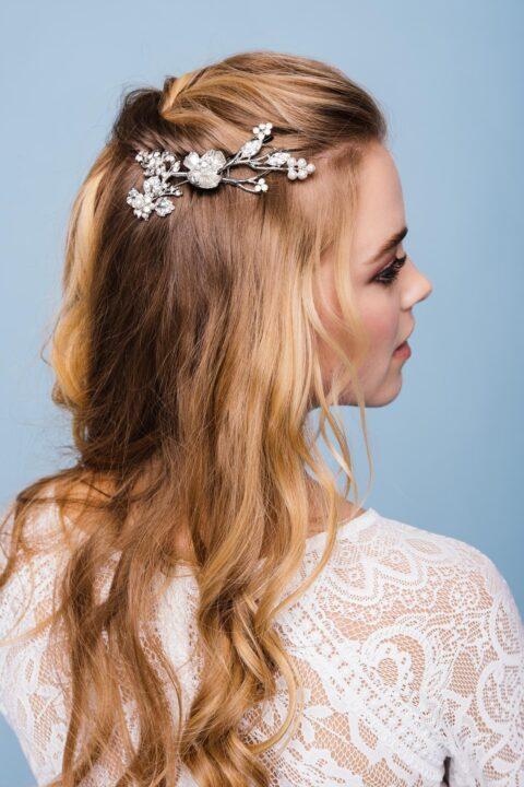 Braut mit Spitzenkleid und filigraner Brosche im Haar d