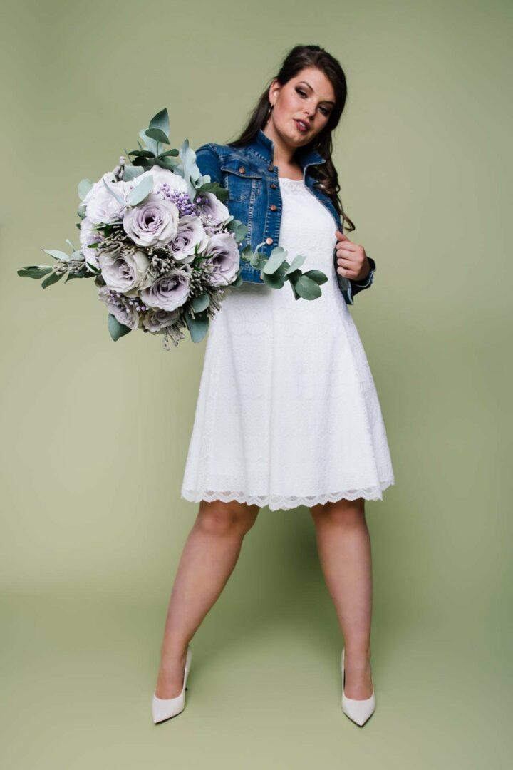 kurzes Brautkleid große Größe mit Jeansjacke und Brautstrauß