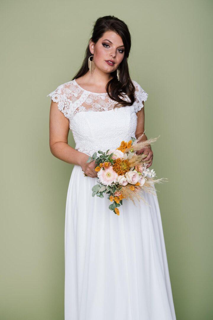 Curvy Bride mit Spitzenmixbolero und Brautstrauß