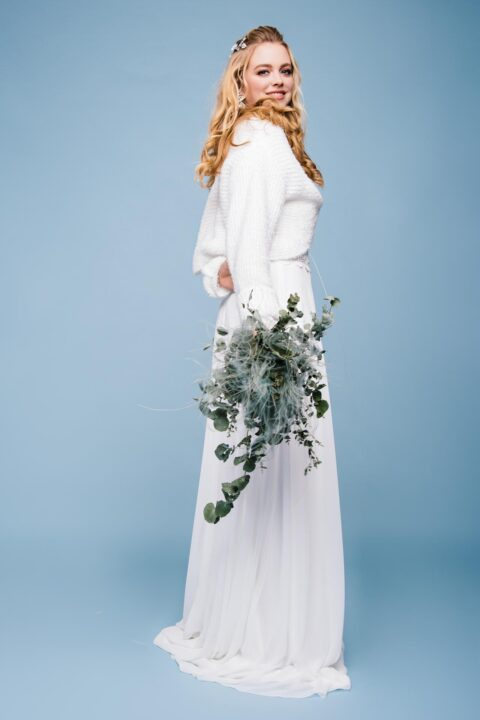 Winterbraut mit Brautstrauß und Braut Pullover aus Strick
