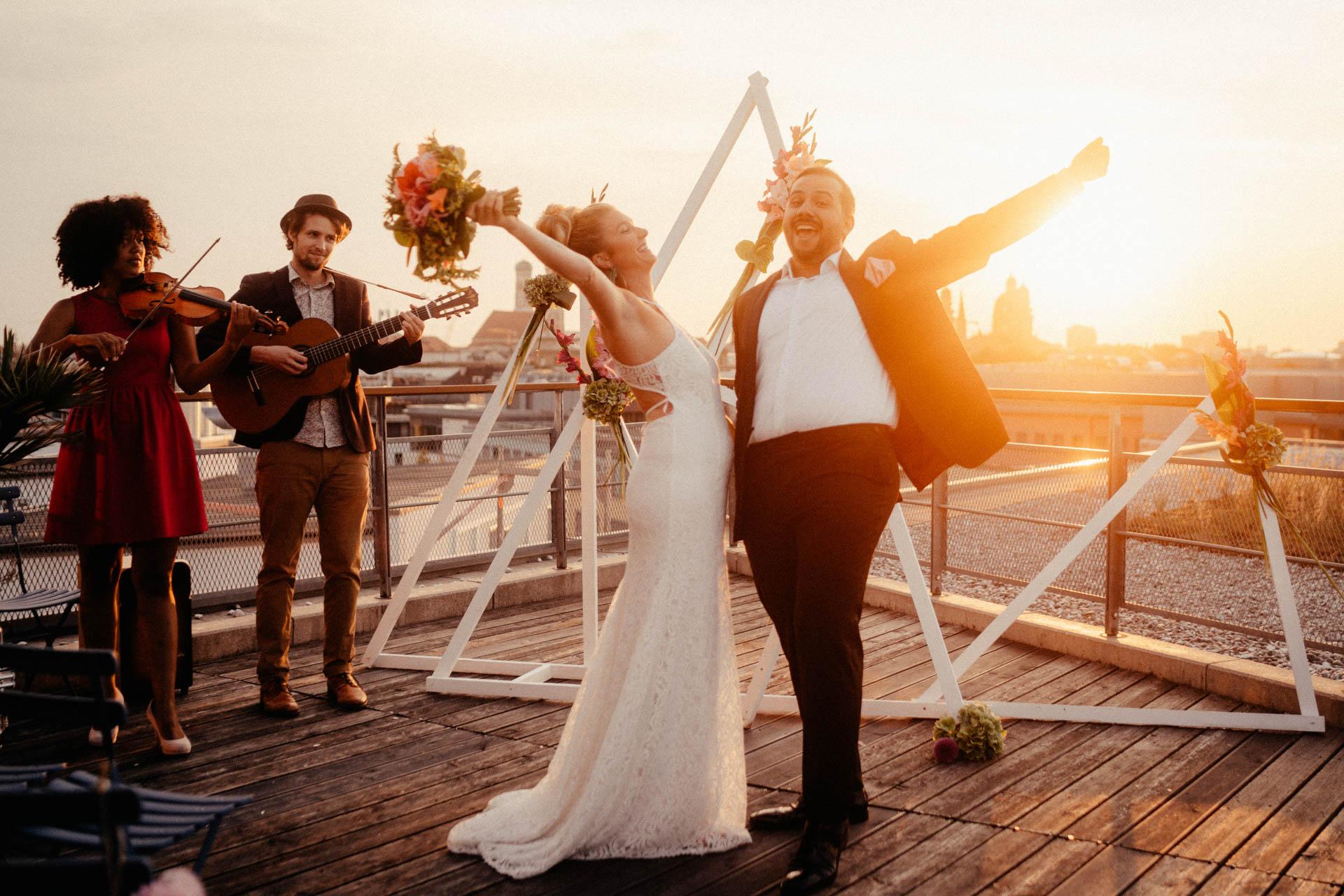 Freie Trauung in München auf der Dachterrasse im Surfers Paradies, glückliches Ehepaar jubelt nach Trauung