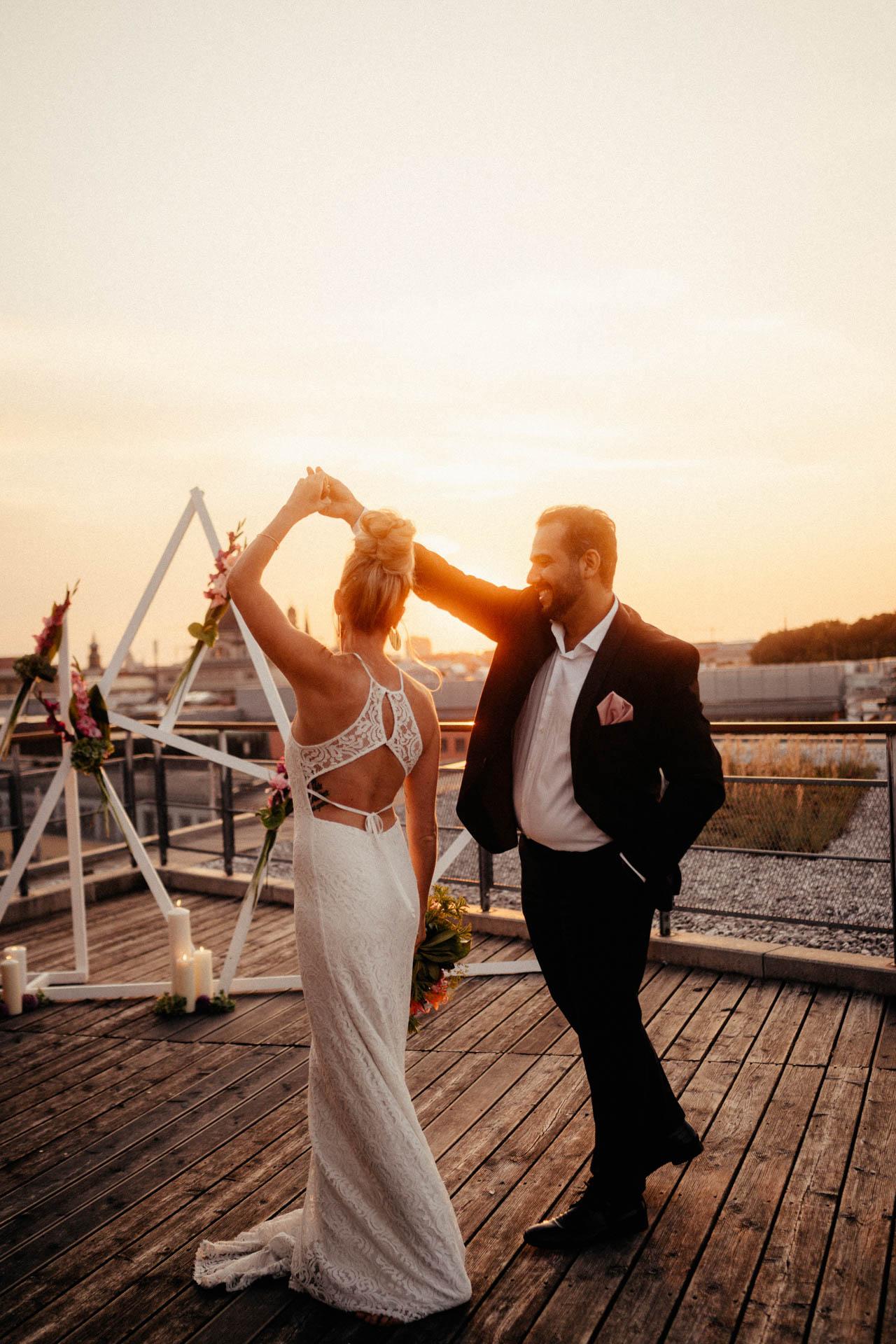 Brautpaar tanzt vor Traumbogen beim Sonnenuntergang