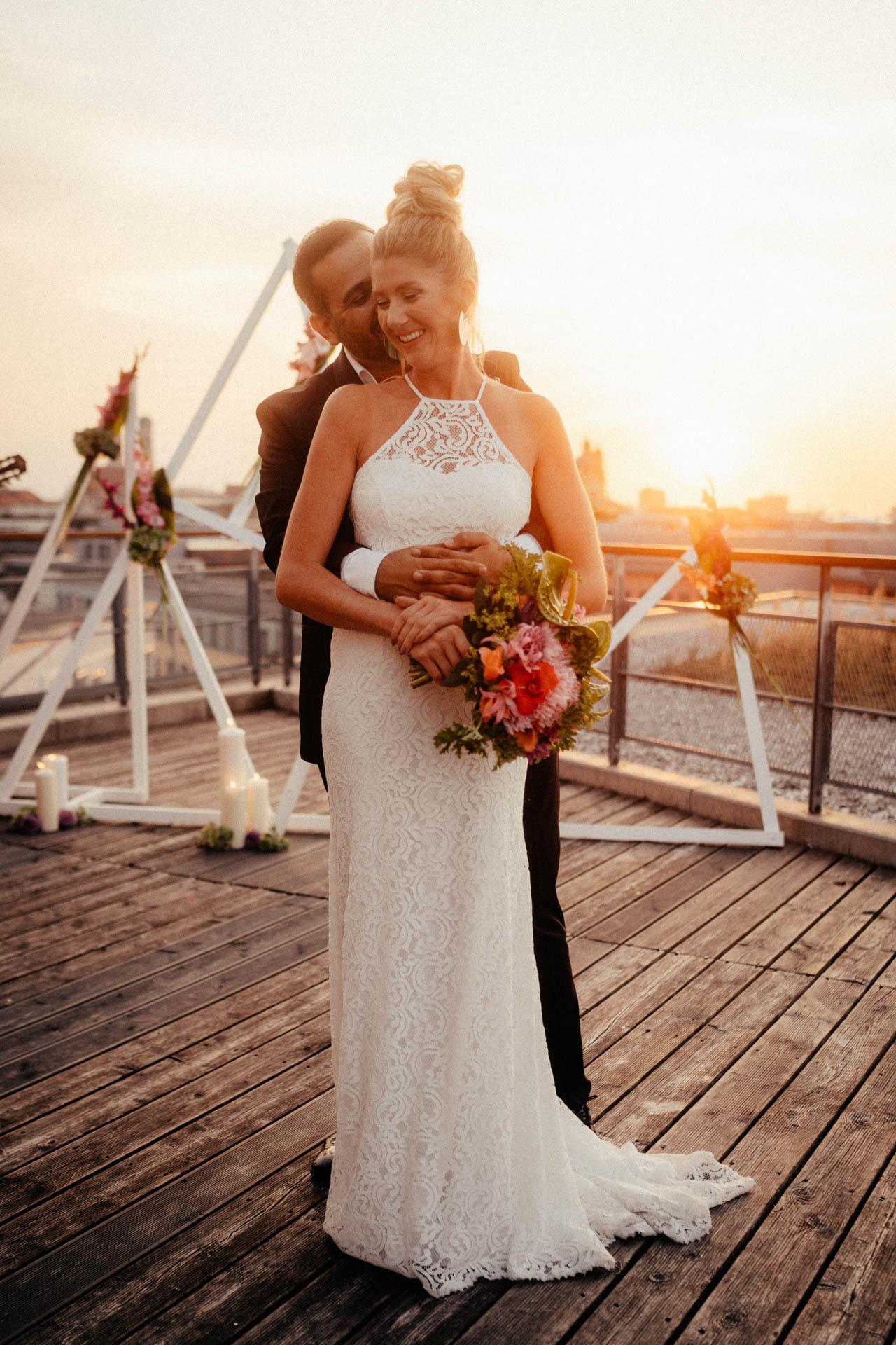 Freie Trauung in München auf der Dachterrasse im Surfers Paradies, Bräutigam umarmt Braut beim Sonnenuntergang