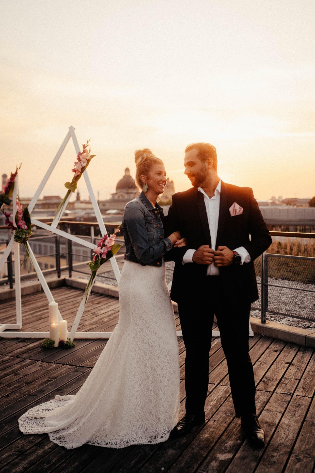 Braut mit Jeansjacke hängt sich bei Bräutigam ein