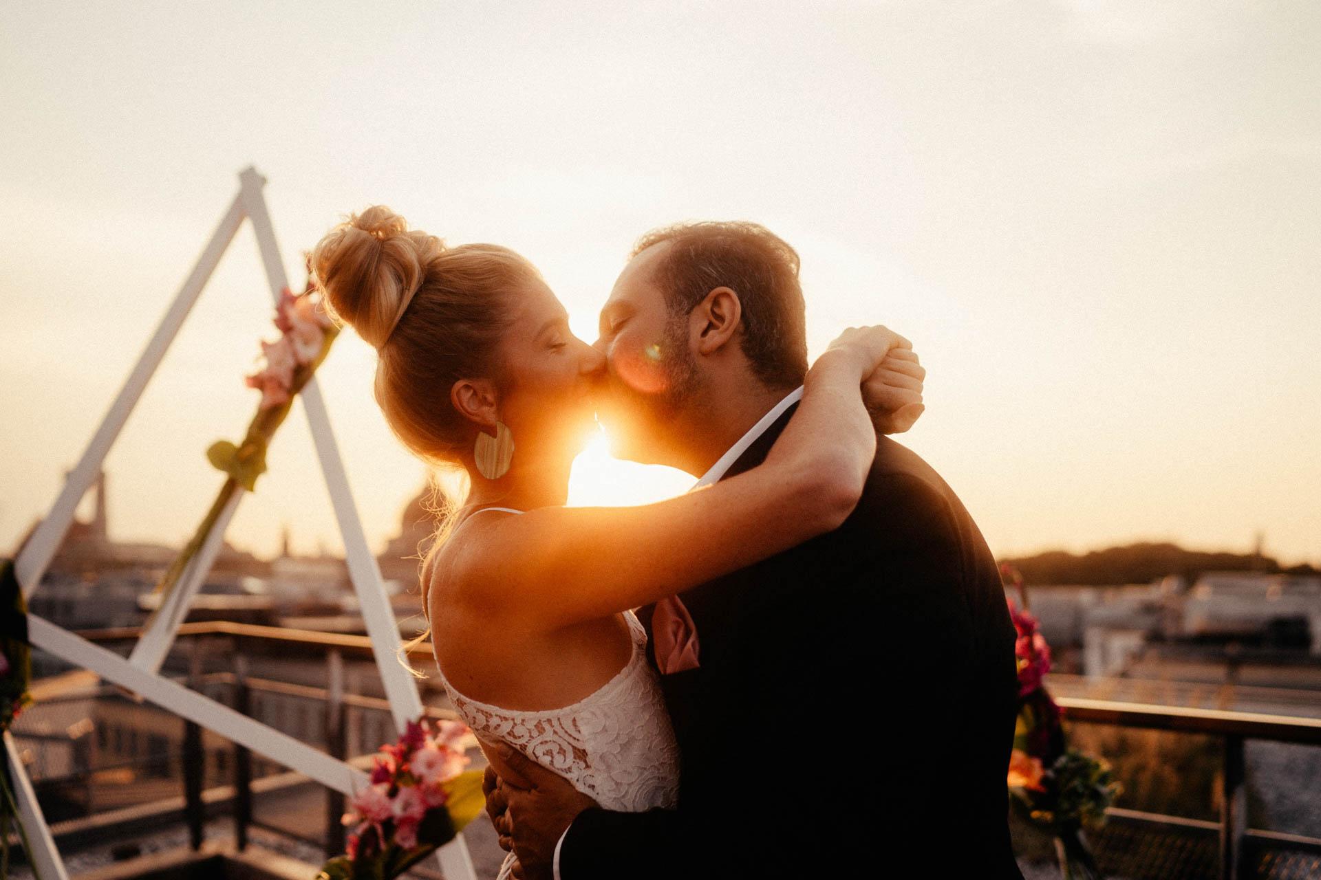 Ehepaar küsst sich nach freier Trauung in München auf der Dachterrasse im Sonnenuntergang
