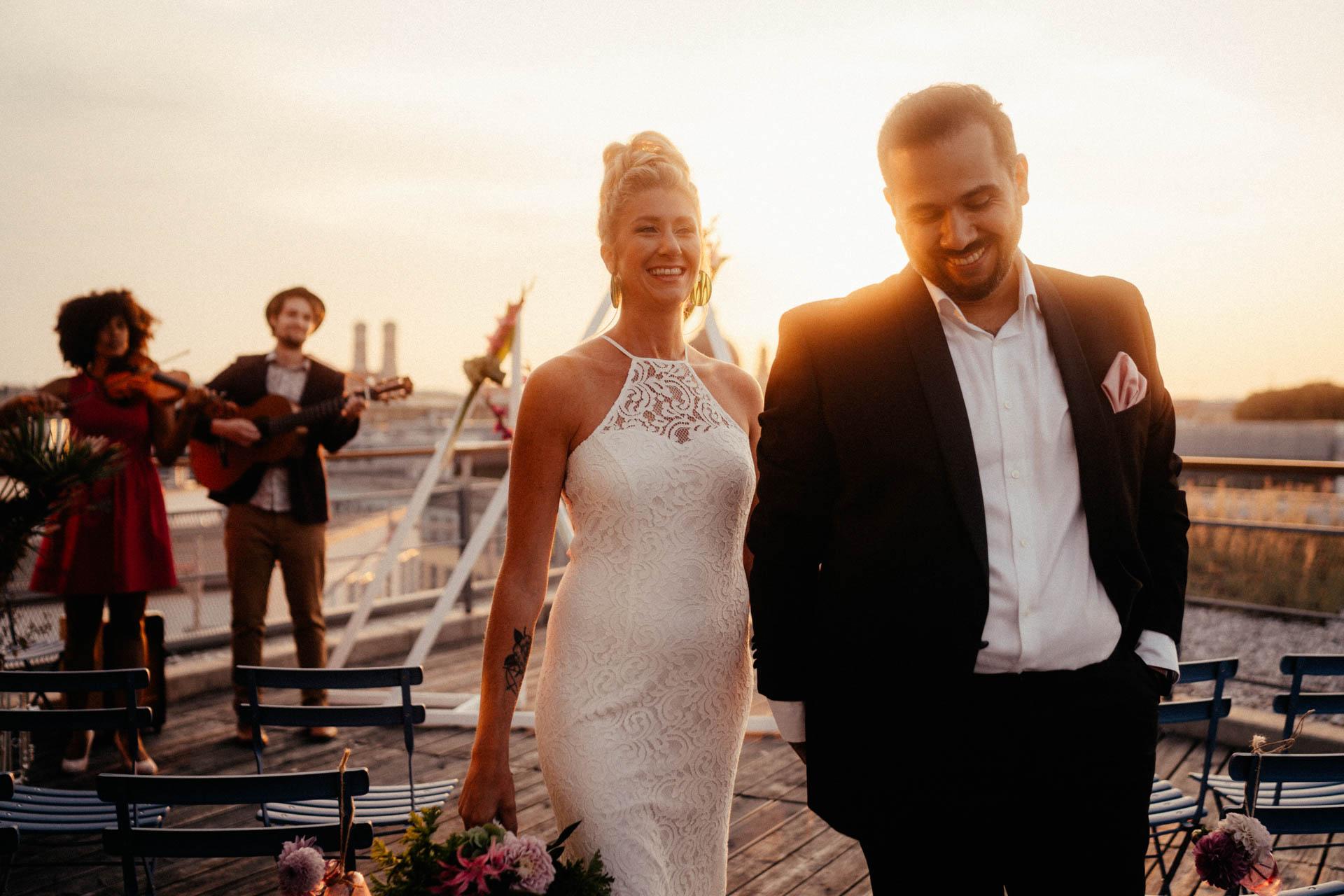 Glücklich strahlendes Brautpaar mit Braut im Spitzenkleid mit Sonnenuntergang im Hintergrund