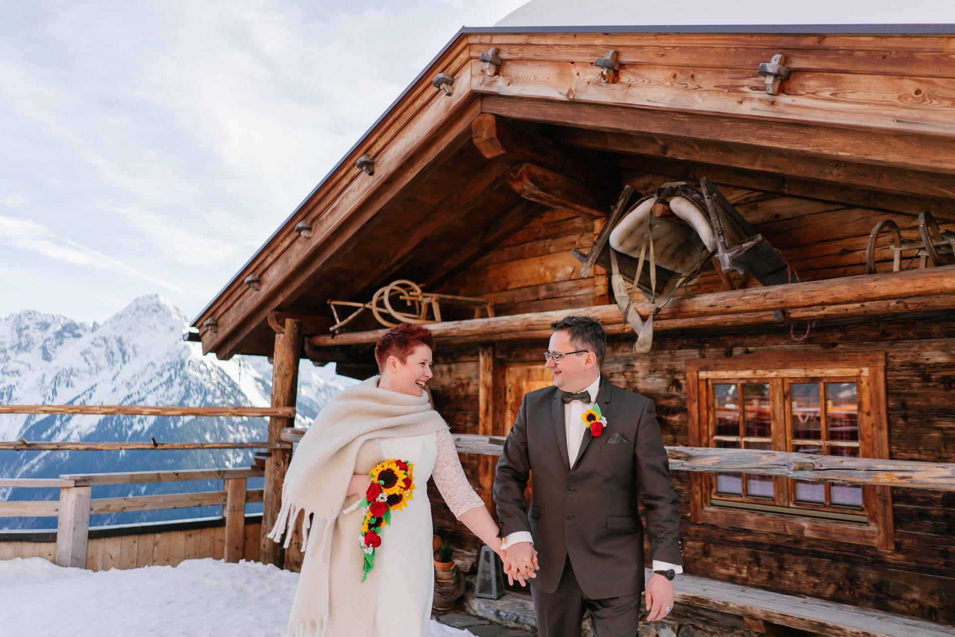 Brautpaar Hand in Hand vor Skihütte im Schnee