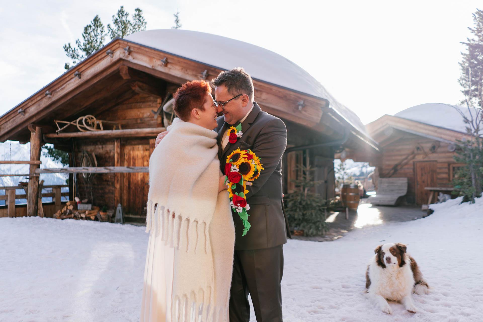Brautpaar glücklich im Schnee neben Hund vor Schneekarthütte