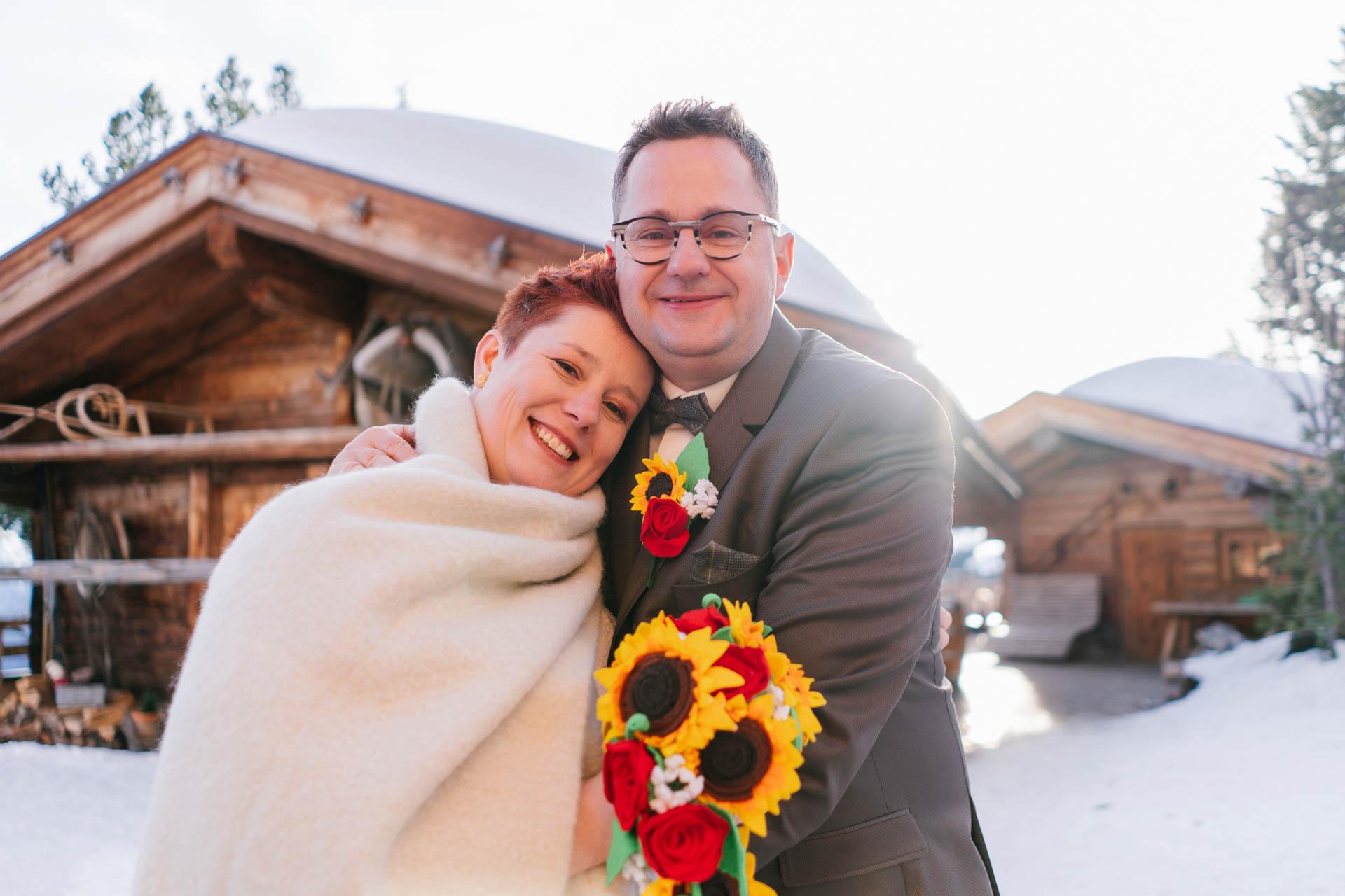 glückliches Brautpaar im Schnee bei Winterhochzeit im Zillertal