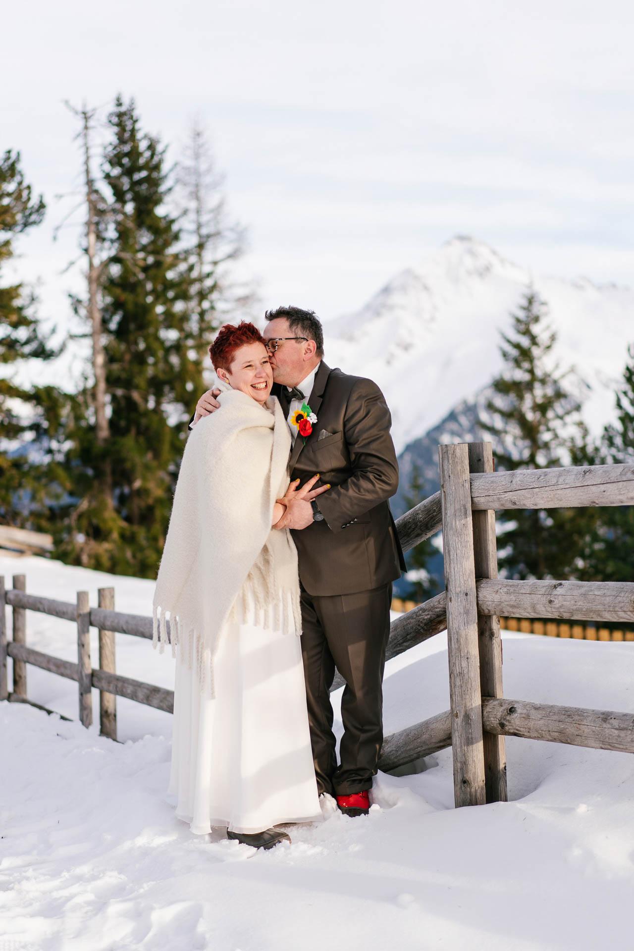Winterhochzeit im Zillertal, Bräutigam küsst Braut glücklich im Schnee