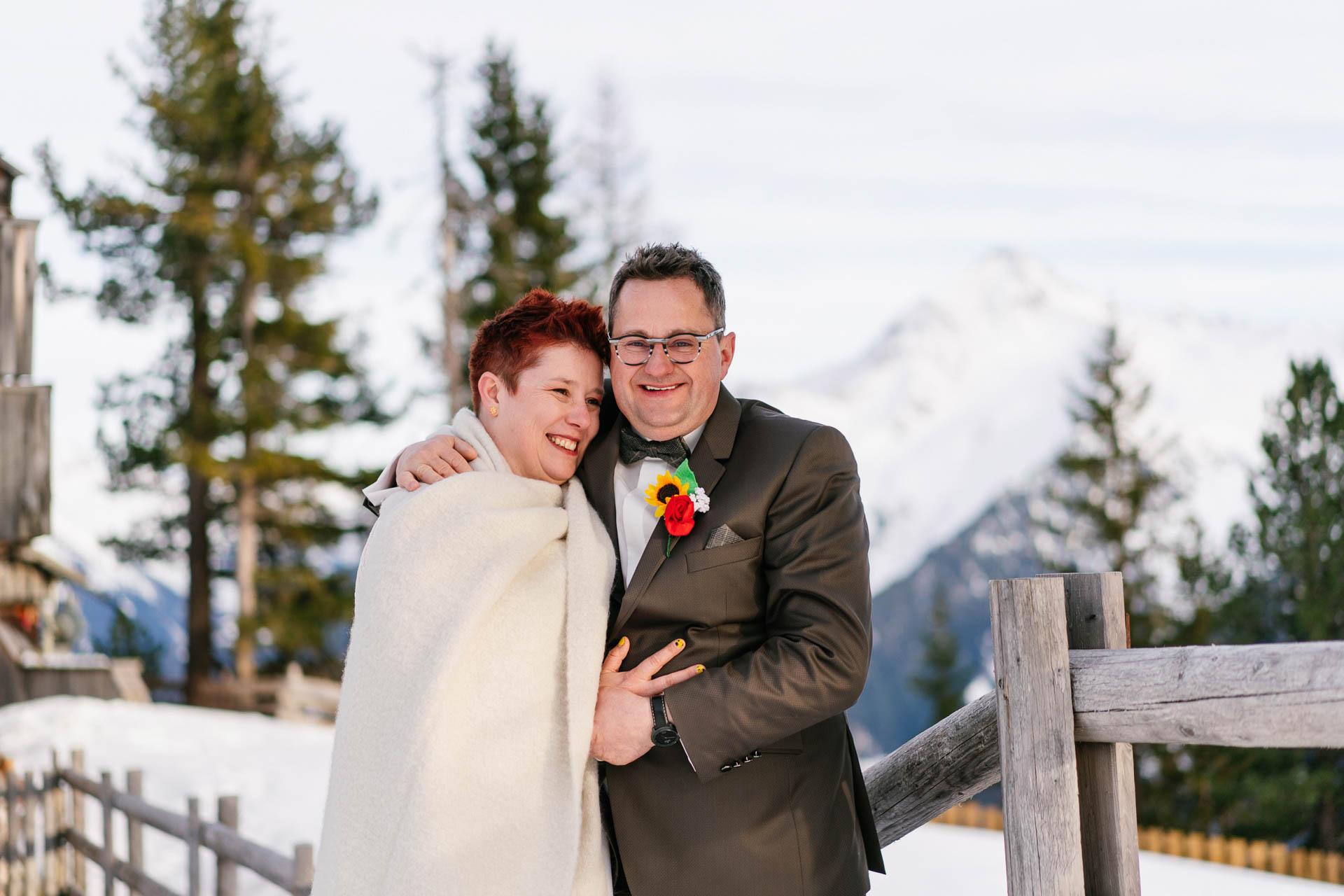 Brautpaar glücklich im Schnee bei Winterhochzeit in den Bergen
