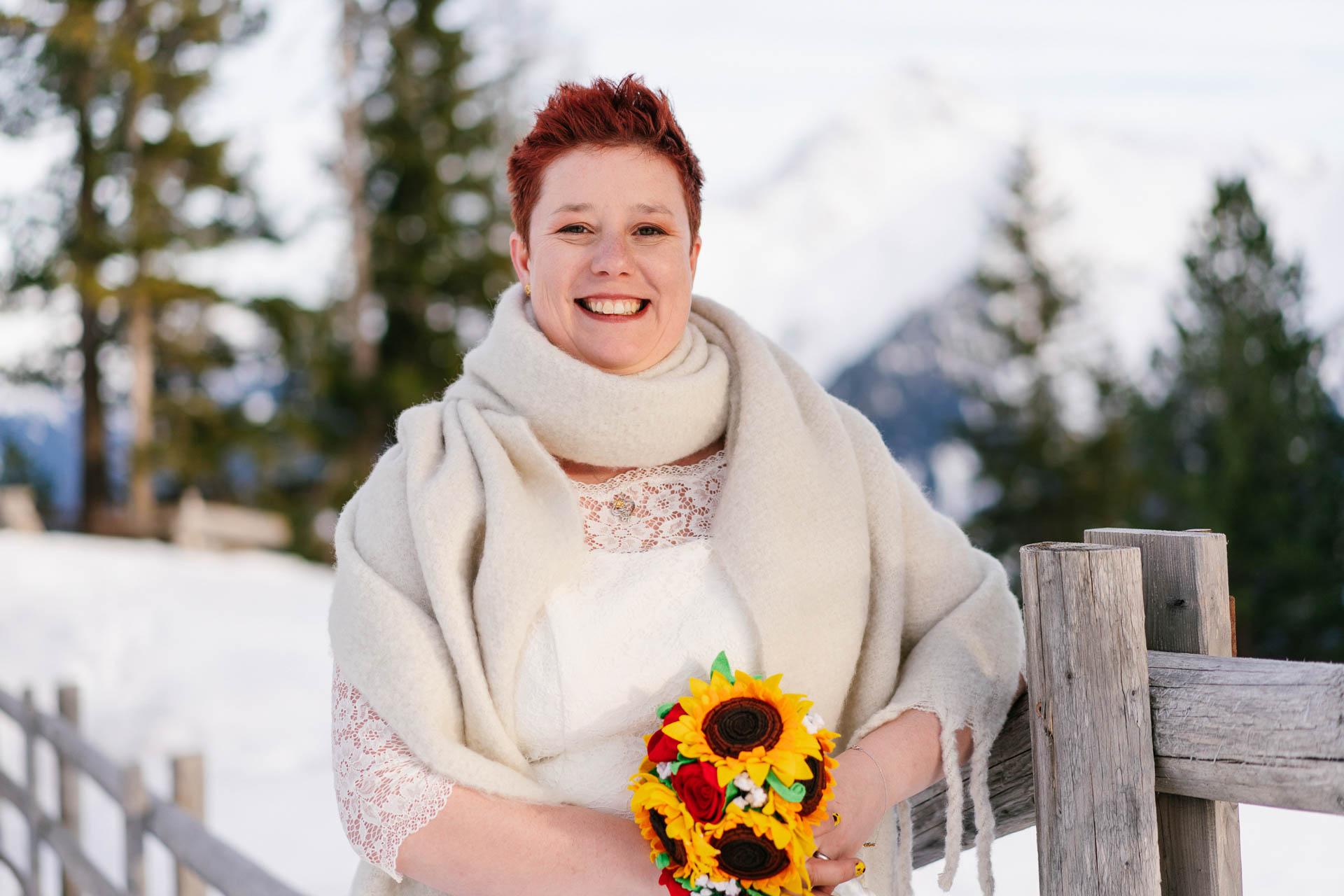 glücklich strahlende Braut mit roten, kurzen Haaren im Schnee