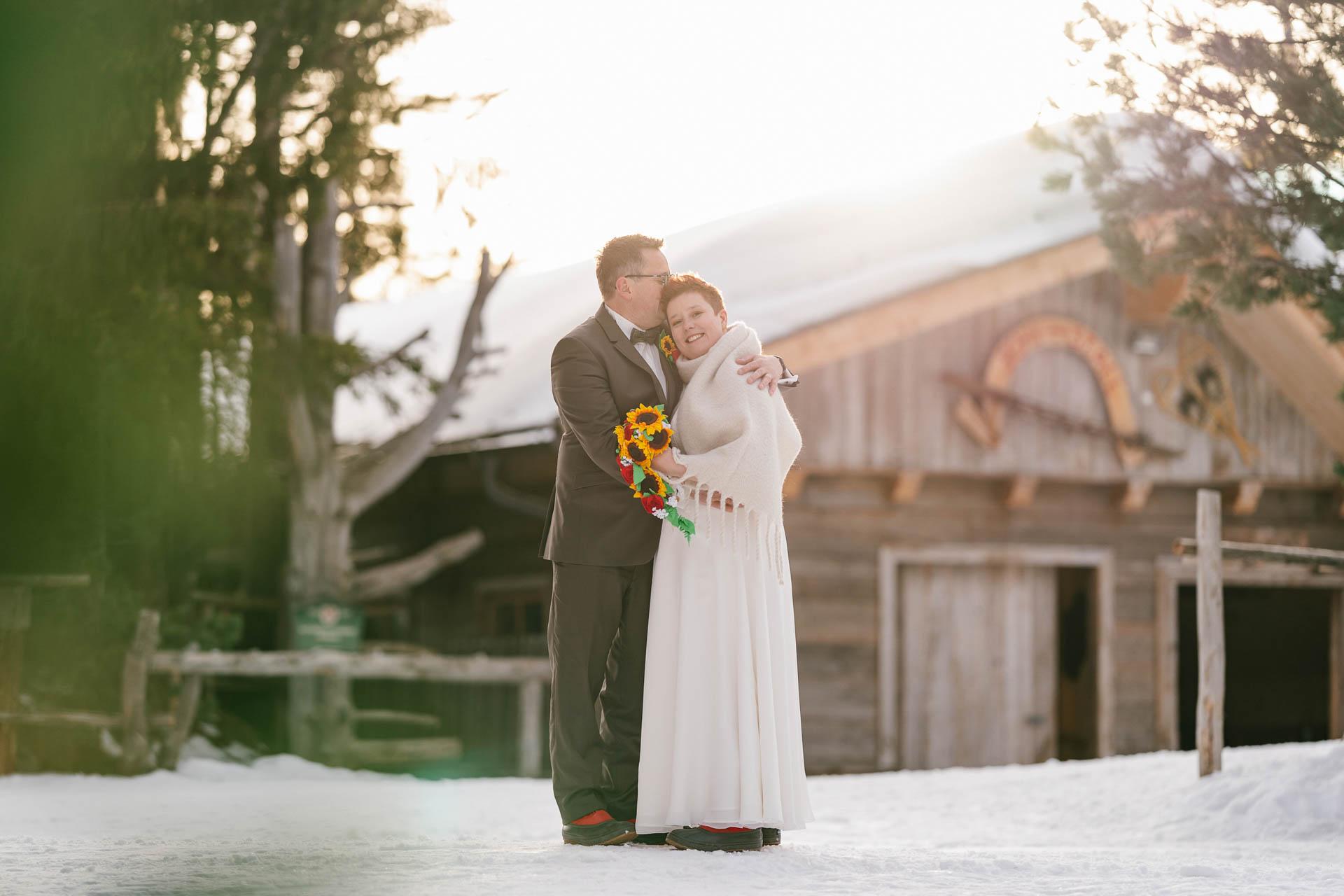 Winterhochzeit im Zillertal, Bräutigam umarmt Braut glücklich im Schnee