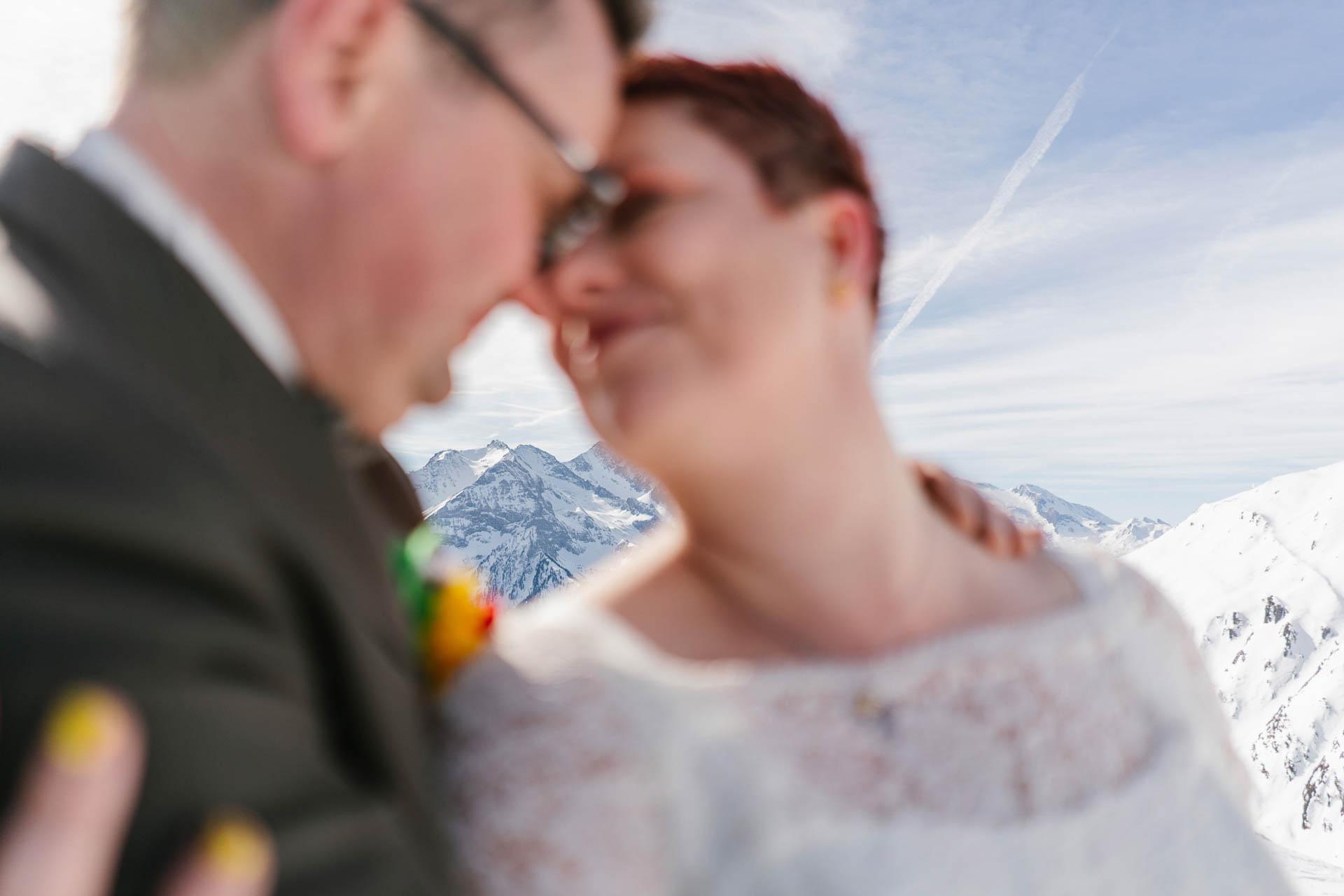 Brautpaar glücklich verträumt Kopf an Kopf im Schneepanorama