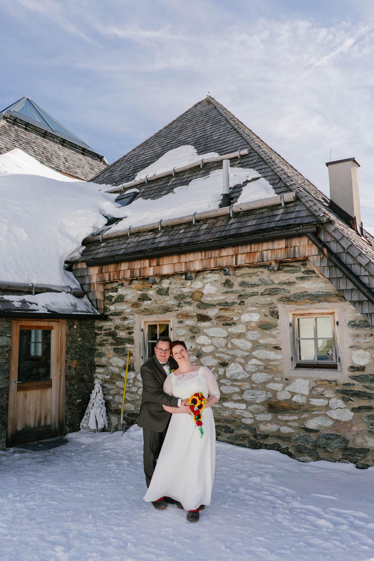 Winterhochzeit im Zillertal, Brautpaar glücklich im Schnee vor Schneekarthütte