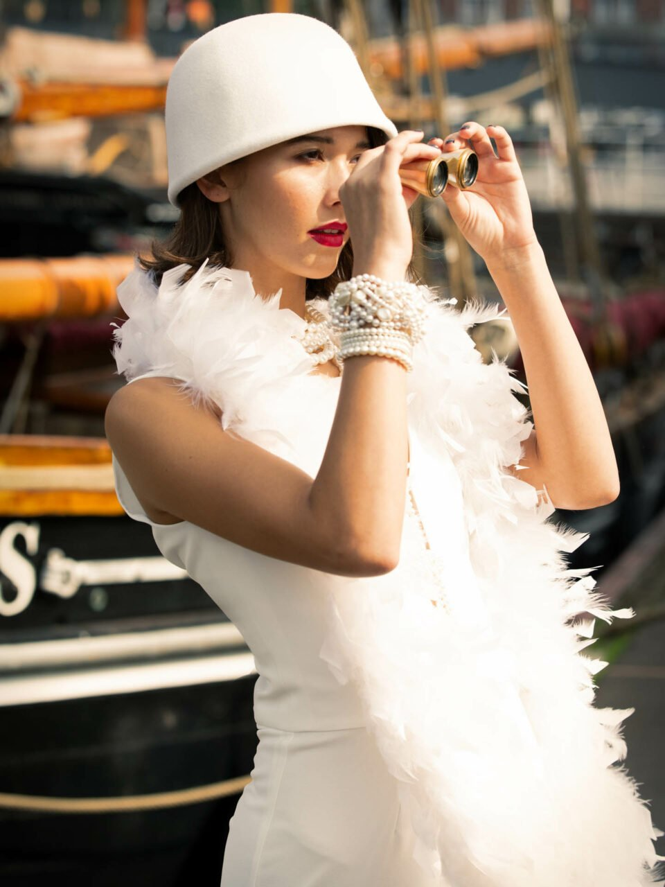 20er Jahre Hochzeitsoutfit mit Hut und Federboa, Braut schaut durchs Fernglas