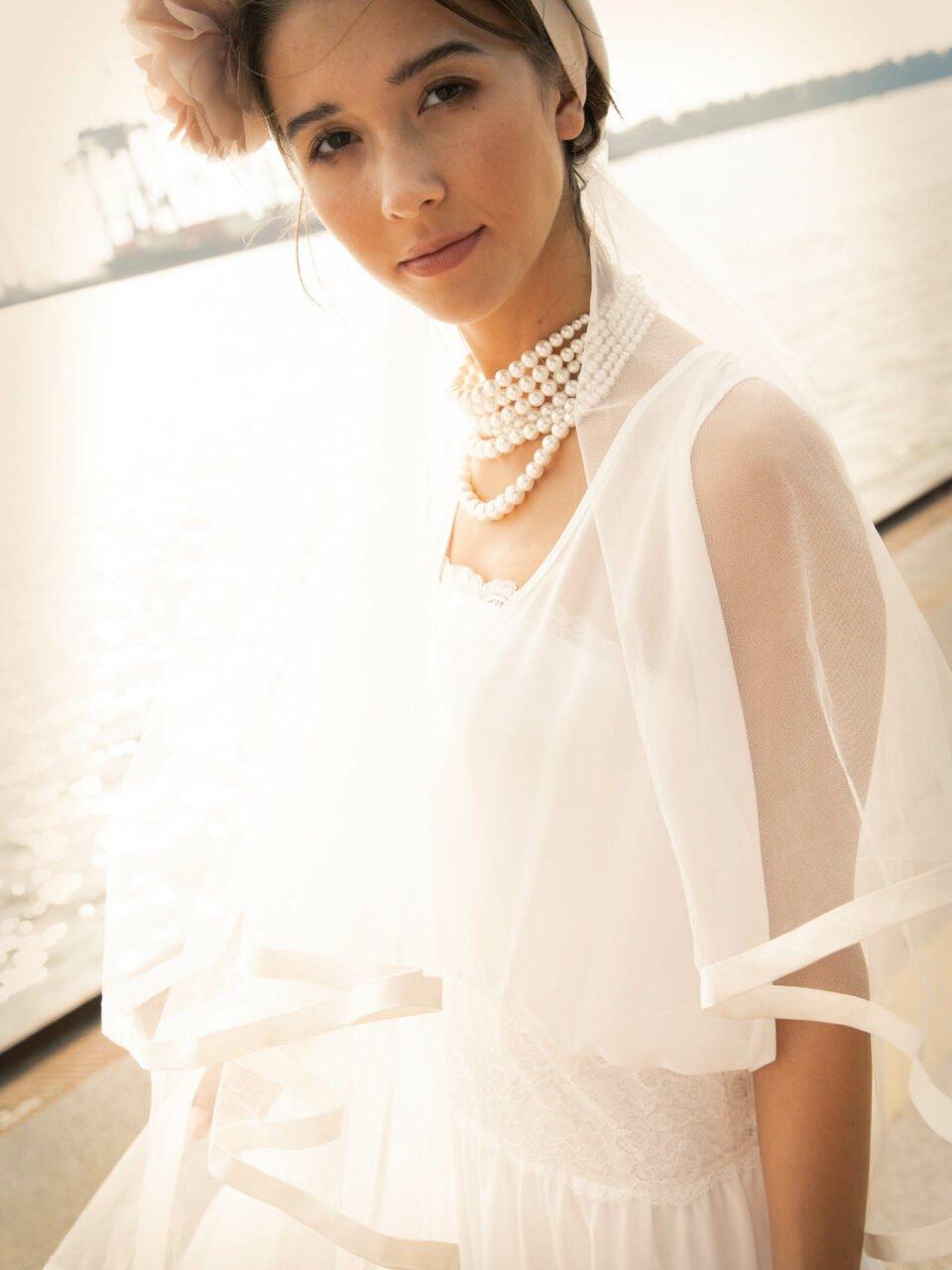 Braut am Wasser mit großer Perlen-Halskette