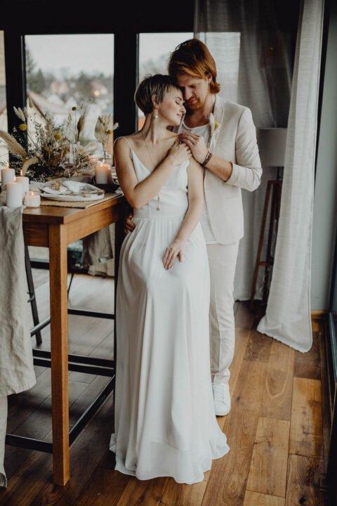 Braut schmiegt sich an Bräutigam