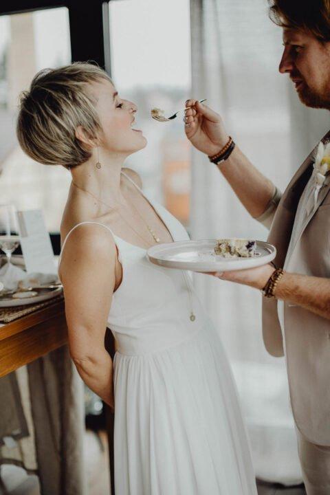 Natürliche Hochzeit, Bräutigam gibt Braut Hochzeitstorte in den Mund