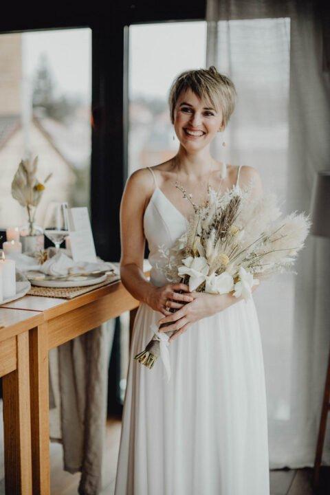 Glücklich strahlende Kurzhaar-Braut mit Trockenblumen