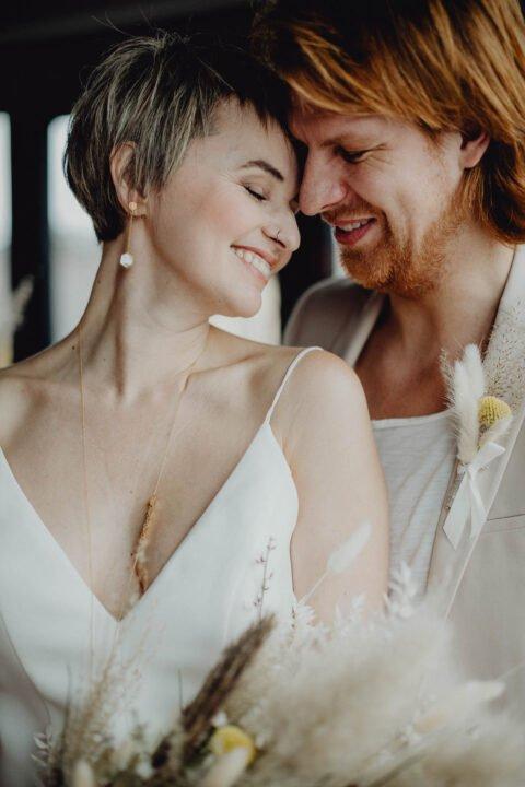 Braut schmiegt sich glücklich an Bräutigam