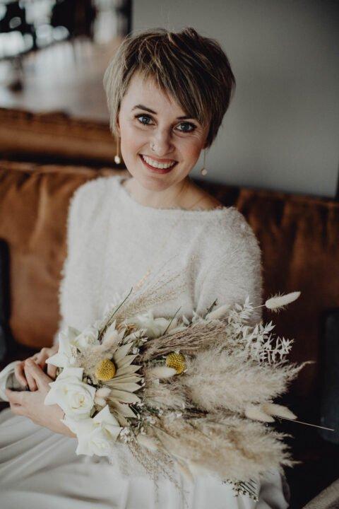Kurzhaar-Braut mit Brautpulli und Trockenblumen