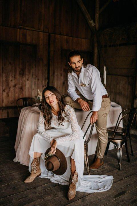 Western Hochzeit, Braut sitzt breitbeinig da und hält Cowboyhut, Bräutigam steht dahinter