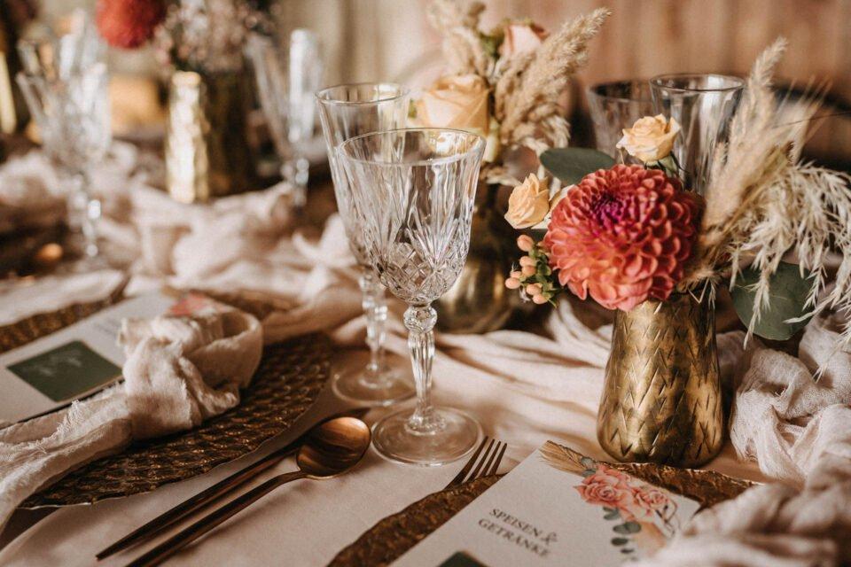 gedeckter Tisch mit Kristallgläsern und goldenen Metallvasen