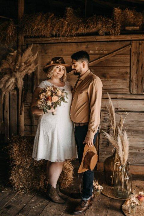 Curvy Braut im kurzen Plus Size Brautkleid mit Brautstrauß und Ehemann