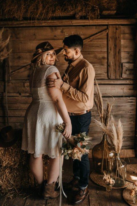 Kurvige Braut im kurzen Spitzenkleid wird von Bräutigam umarmt