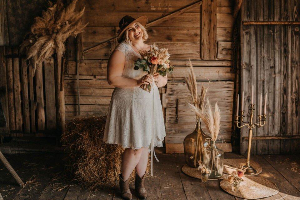 Lachende Curvy Braut im kurzen Plus Size Brautkleid mit Brautstrauß
