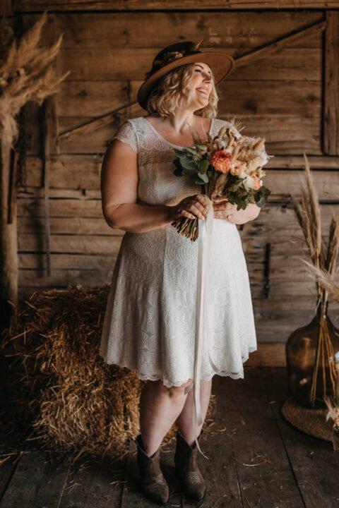 Lachende Braut im kurzen Plus Size Brautkleid mit Brautstrauß