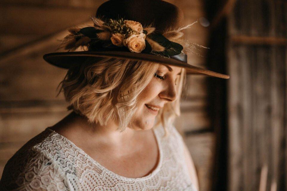 Braut trägt Cowboyhut mit Blumenschmuck