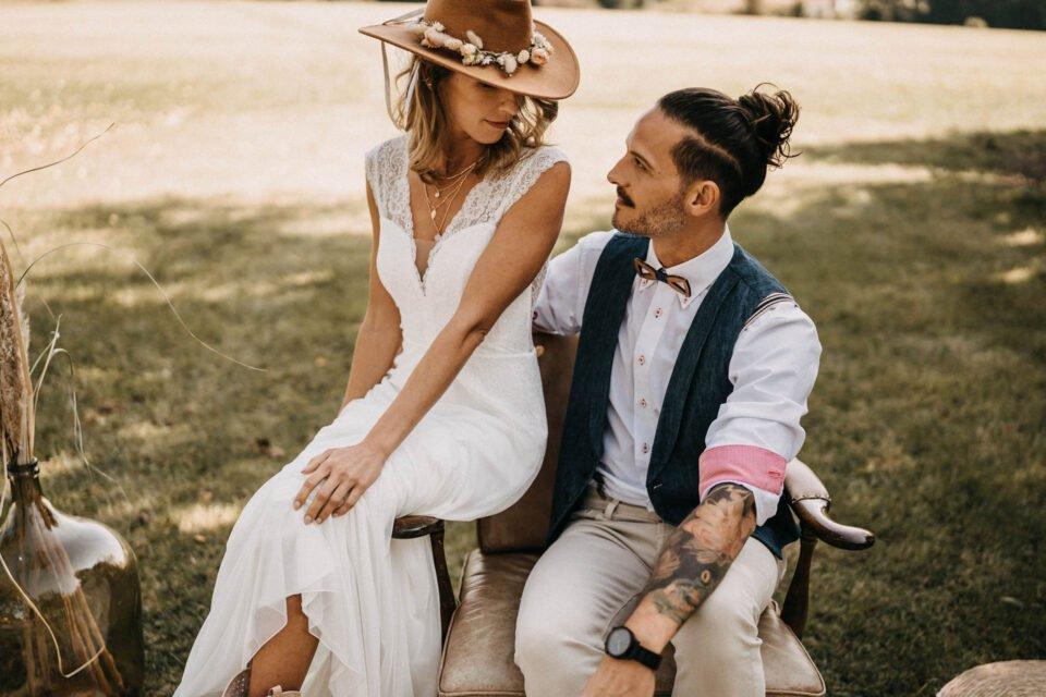 Boho Brautpaar schaut sich an, Braut trägt Cowboyhut