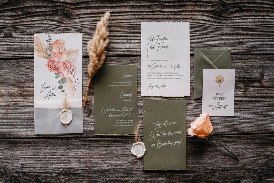 Hochzeitspapeterie auf Holztisch mit Blumen