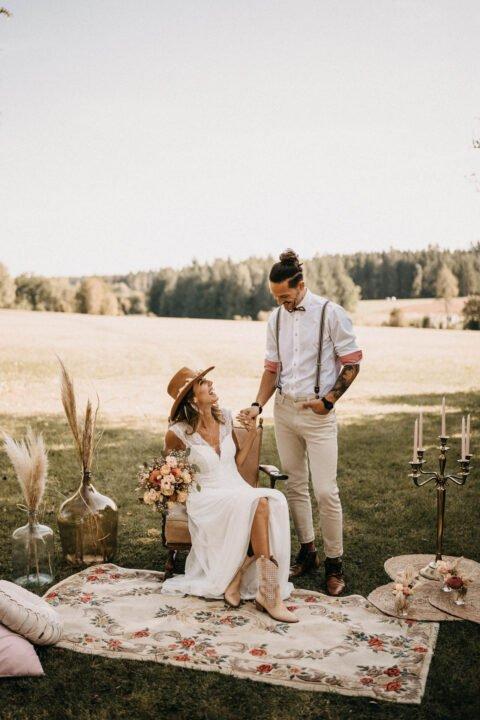 Western Hochzeit, Inspiration mit Braut in Cowboystiefeln in Cowboyhut auf Wiese mit tätowiertem Bräutigam