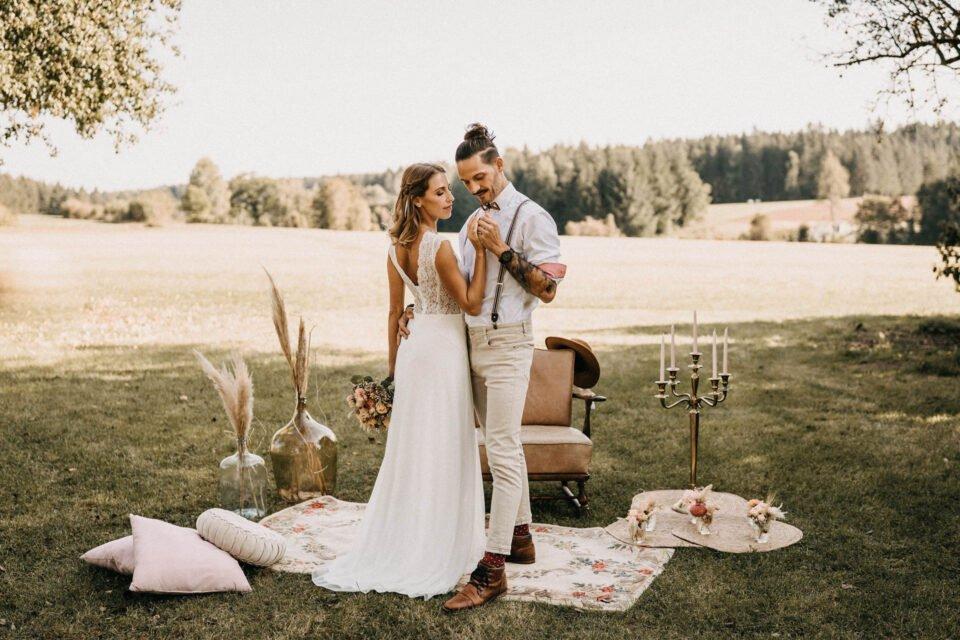Boho Brautpaar auf einem Teppich auf der Wiese