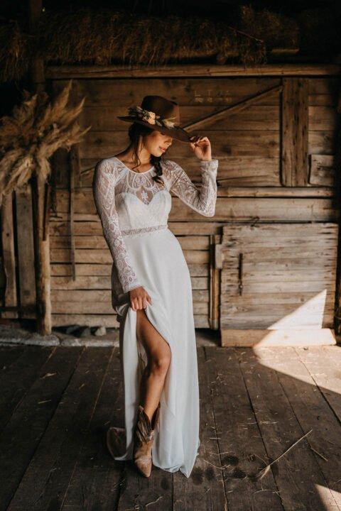 Braut im Countrystyle im Spitzenkleid mit Cowboyhut und Stiefeln