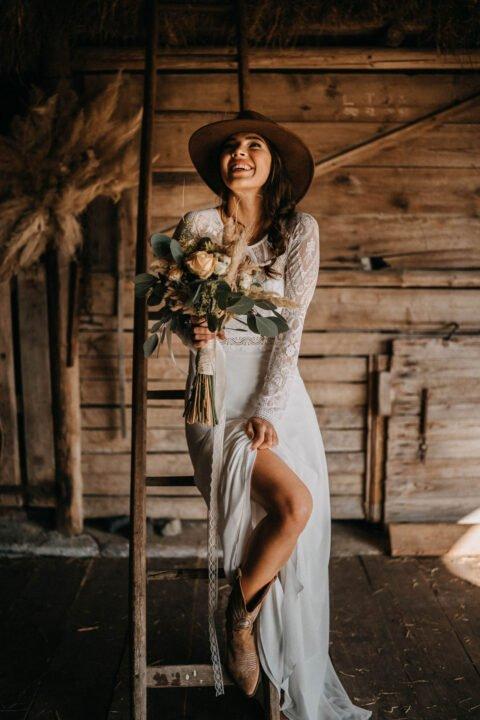 Glückliche Boho Braut mit Brautstrauß