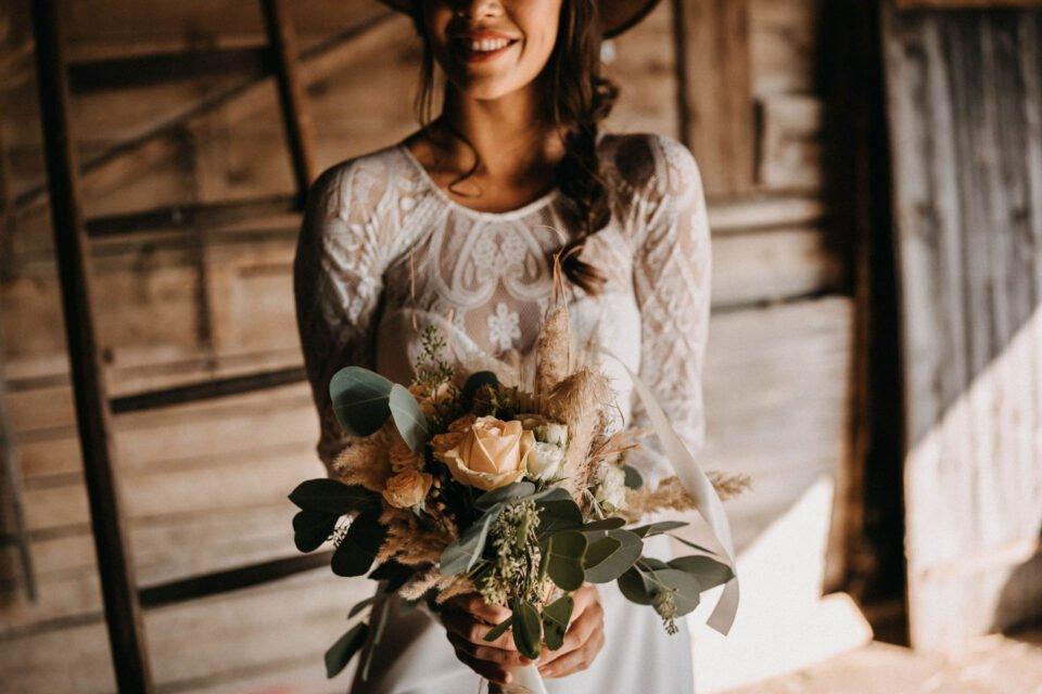 Detailaufnahme Brautstrauß an Braut im Spitzenkleid