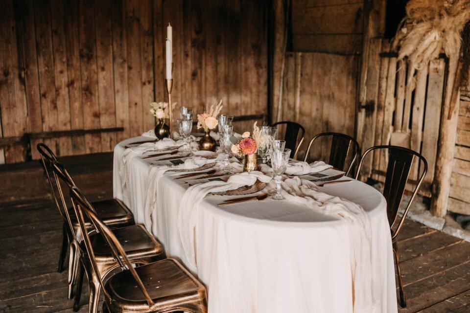 eingedeckter Hochzeitstisch in der Scheune