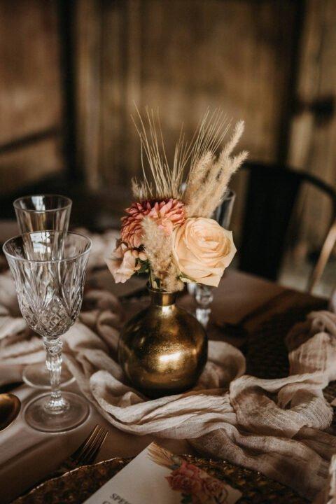 Rosen und Trockenblumen in goldener Vasen als Tischdeko bei Hochzeit