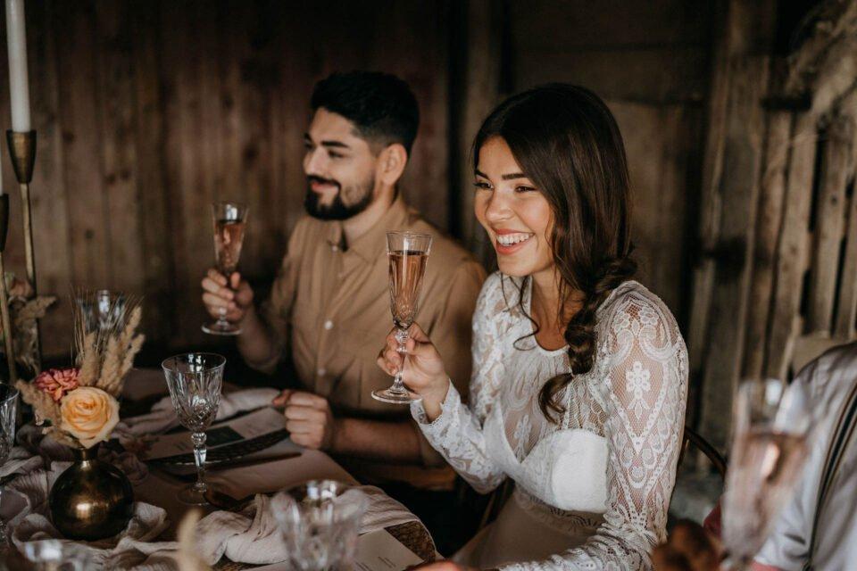 Braut und Bräutigam glücklich mit Sektglas in der Hand am Tisch