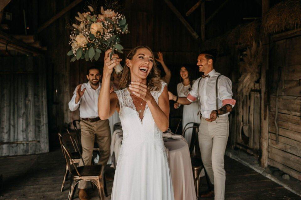 lachende Braut schmeißt Brautstrauß in der Scheune