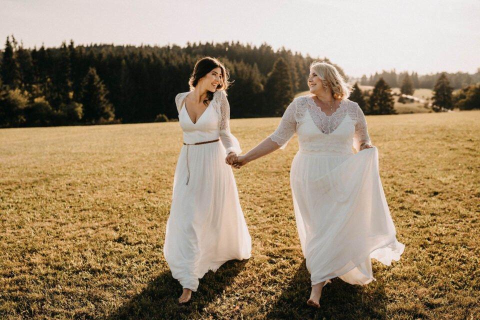 Zwei Bräute im schlichten Brautkleid auf der Wiese