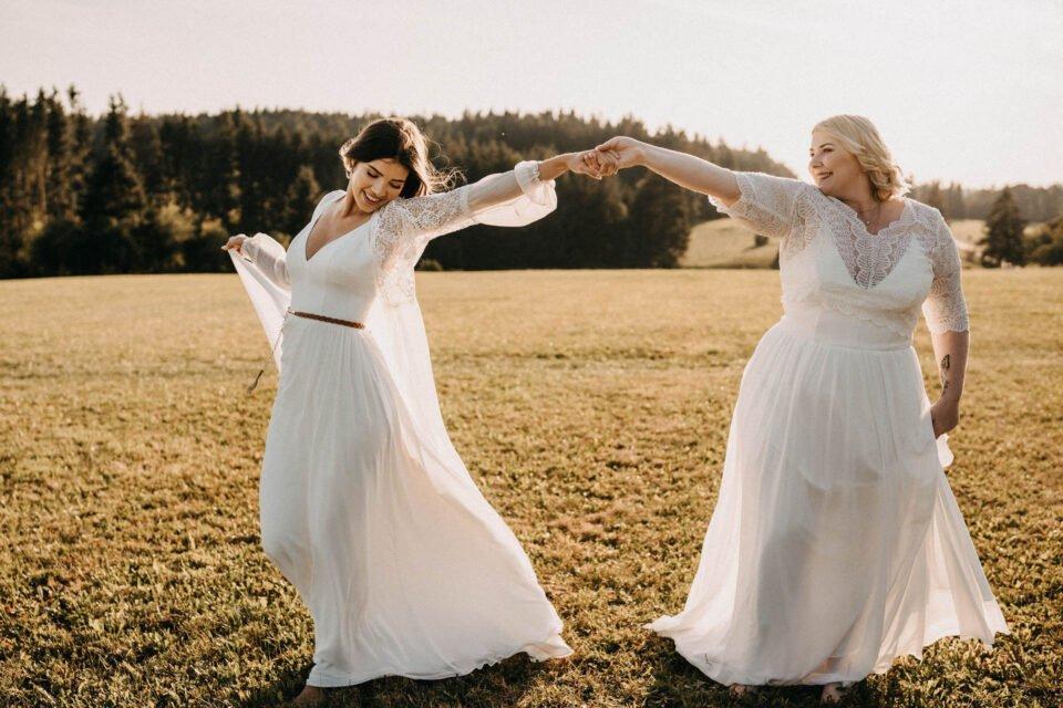 Zwei Bräute Hand in Hand im schlichten Brautkleid