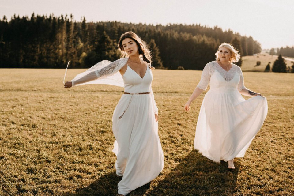 zwei Bräute auf der Wiese im Brautkleid mit Spaghettiträgern